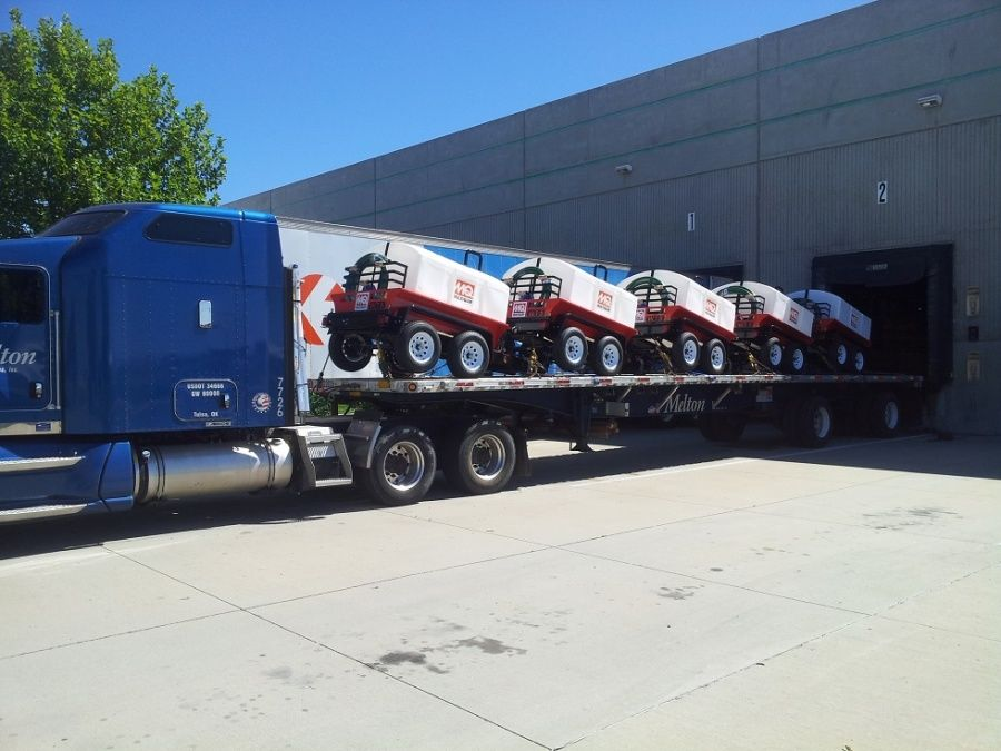 Melton flatbed trailer loaded delivering small portable spray tank trailers