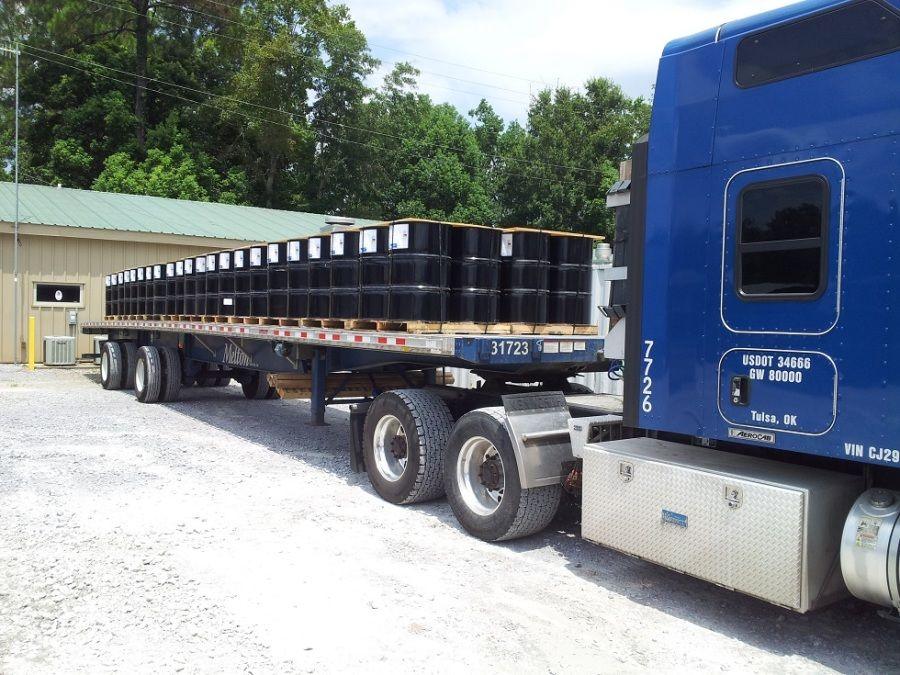 flatbed trailer loaded with barrels of resin oil for drilling rigs