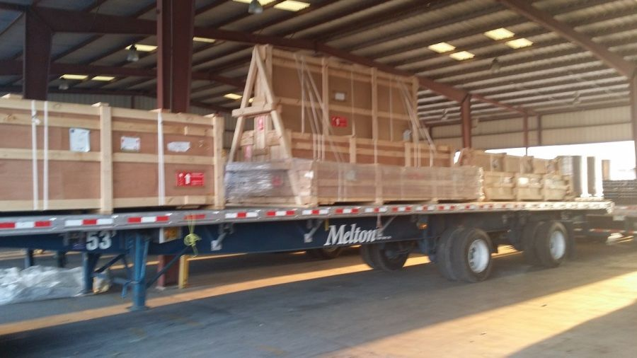Melton flatbed trailer loaded with crated glass ready to be tarped and strapped