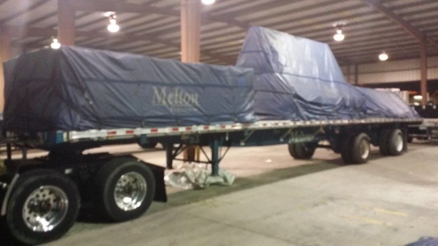Melton flatbed trailer loaded with crated glass tarped and strapped