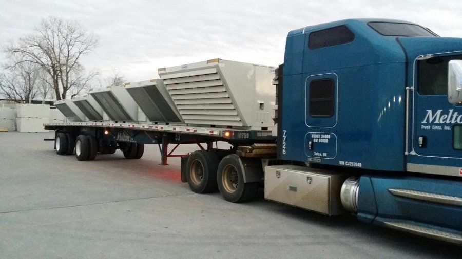blue flatbed melton truck loaded with industrial air conditioning units strapped to it