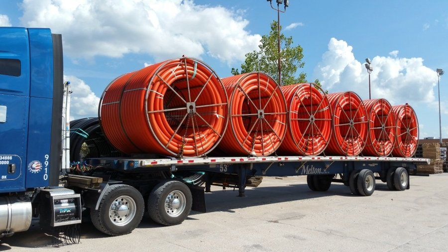 flatbed trailer loaded with reels of plastic hose