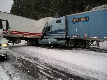 trucking accident crash blue Werner Enterprises truck smashed into the side of another trailer on icy slippery snowy roads