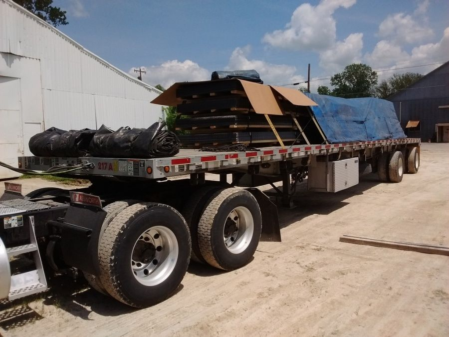 steel grates loaded strapped and tarped on flatbed trailer