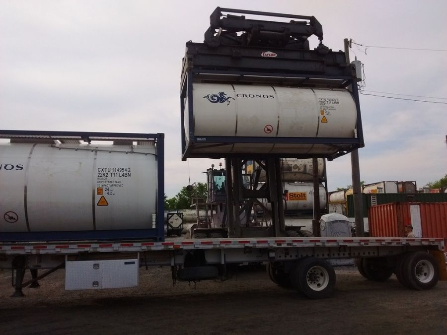 empty container tanks being loaded and chained on a flatbed trailer