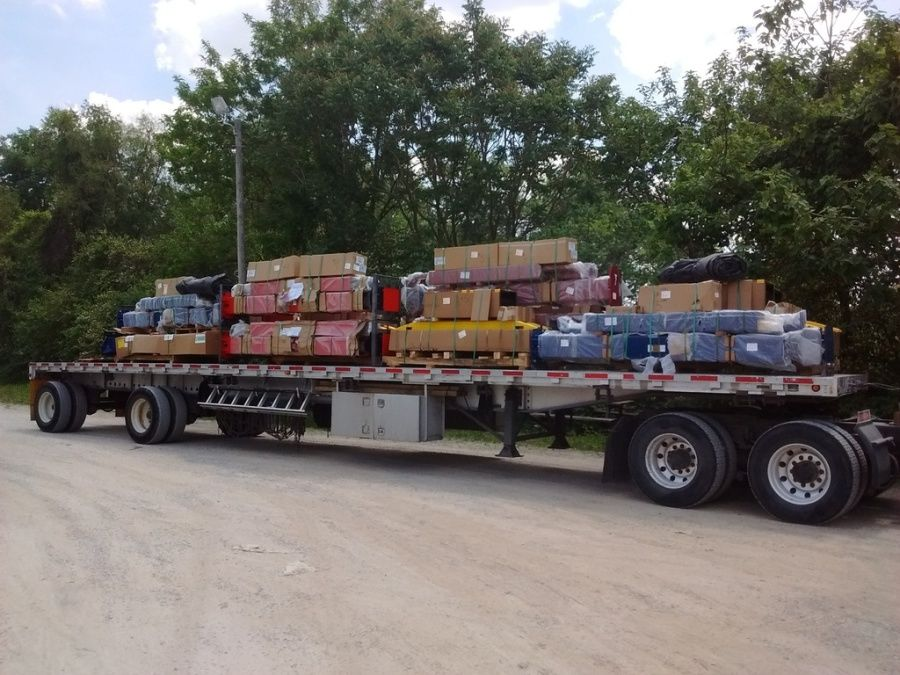 flatbed trailer loaded with automotive lifts strapped all crazy-like