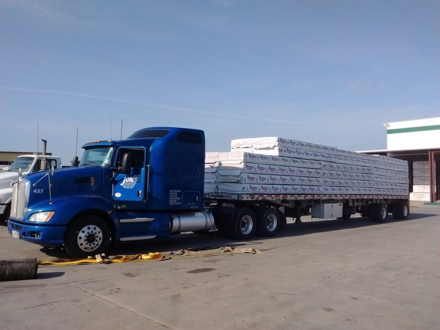 blue Jones flatbed trailer loaded with lumber