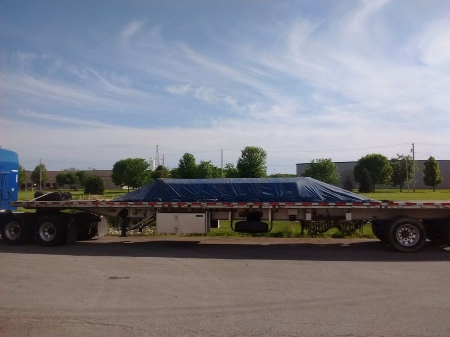 flat steel loaded, tarped and strapped on flatbed trailer at Olympic Steel