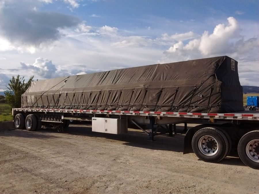 load of plywood tarped and strapped on a flatbed trailer