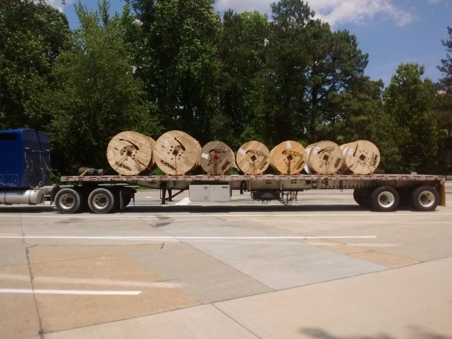 flatbed loaded and chained with cable reels eyes cross-wise