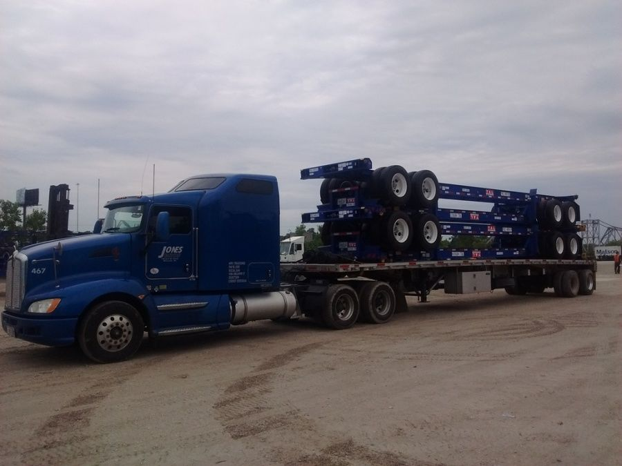 flatbed trailer being loaded with flatbed trailer chassis