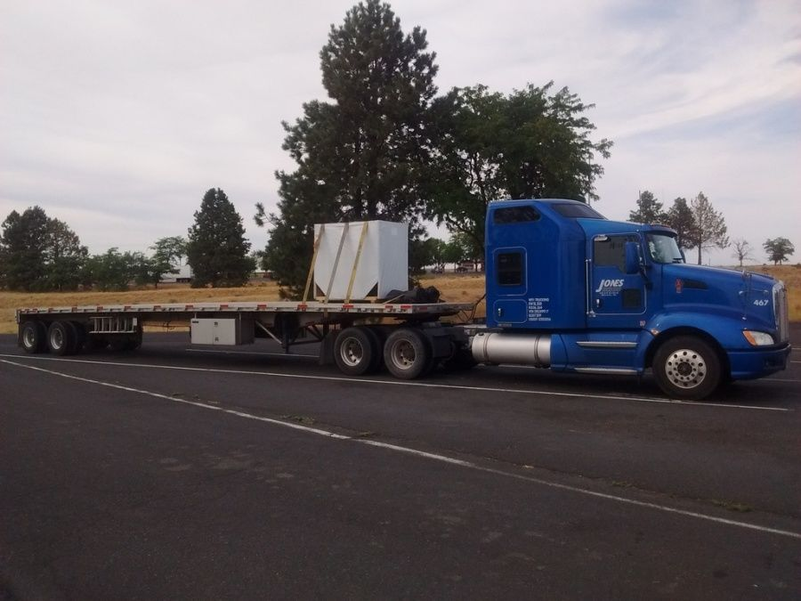 CAT engine loaded and strapped on flatbed trailer