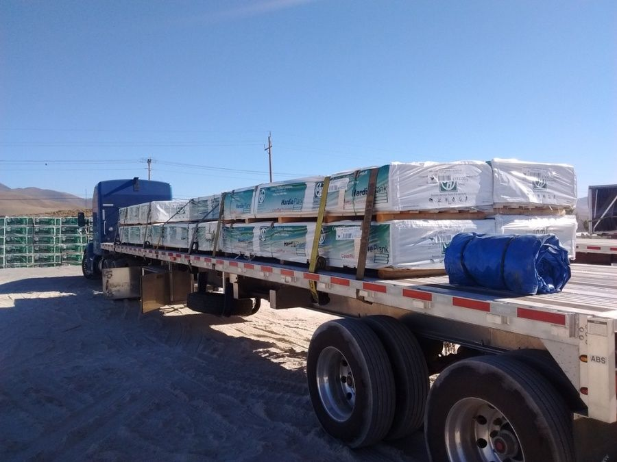pallets of siding material for construction site loaded and strapped on flatbed trailer