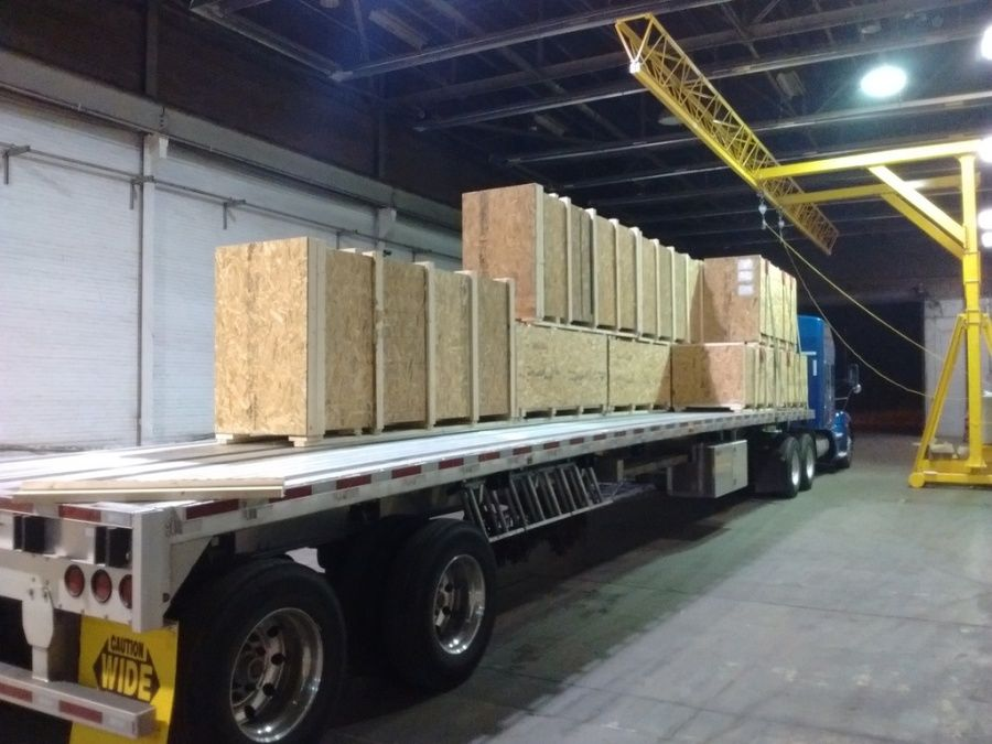 crates of siding panels for new hospital construction being loaded on flatbed trailer