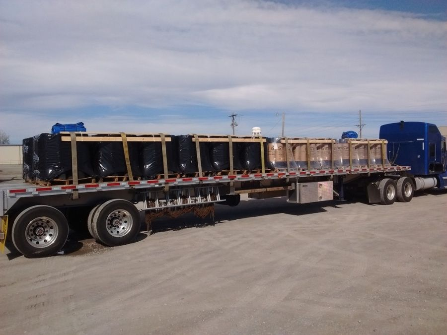 pallets of rolls of roofing material loaded and strapped on flatbed trailer with v-boards