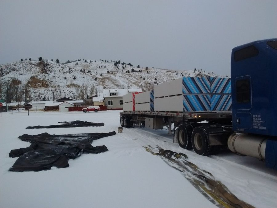 truck driver removing tarps and getting ready to unload flatbed trailer in the snow
