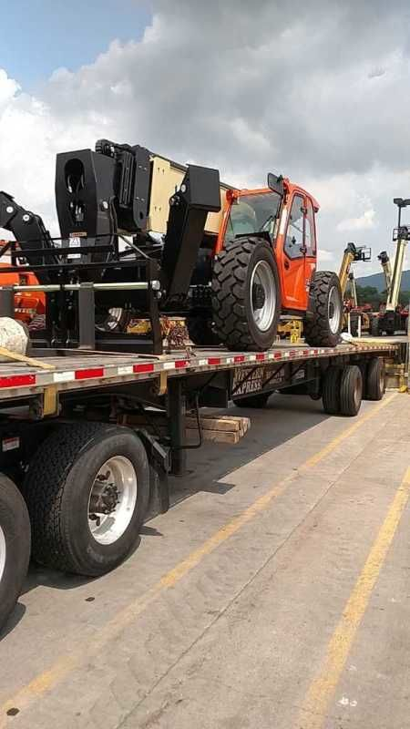 brand new boom crane loaded on flatbed trailer