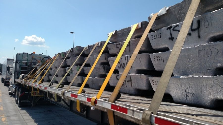 metal slabs loaded and strapped on flatbed trailer