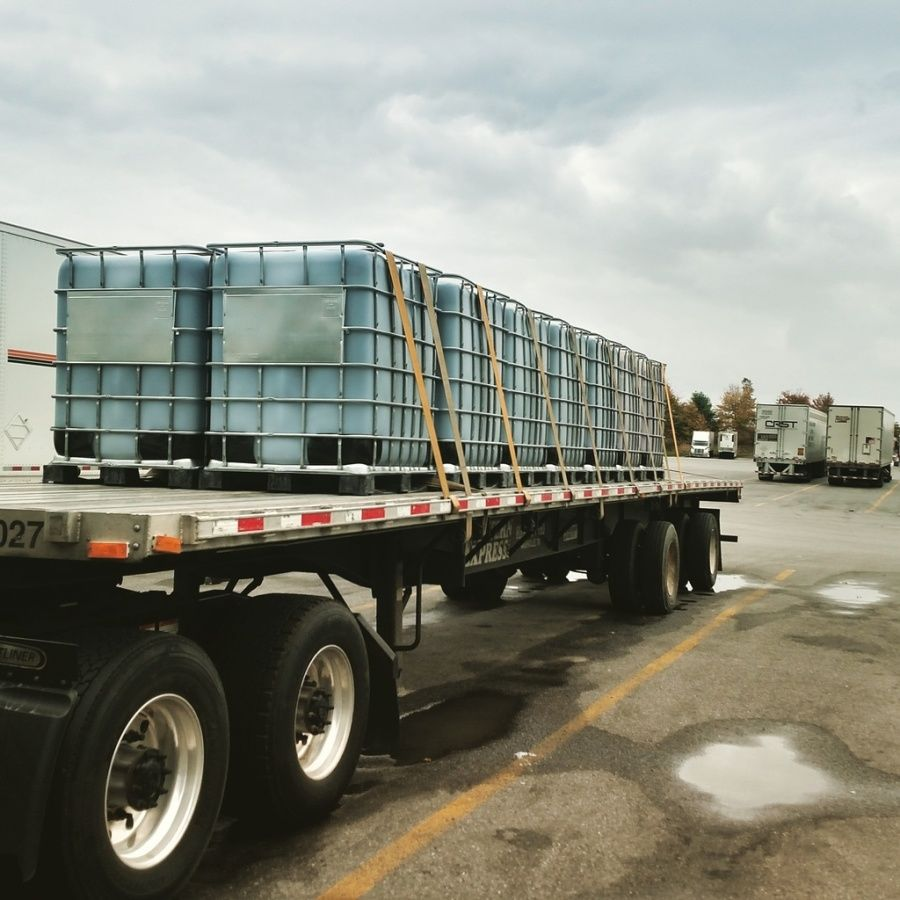 liquid storage bins strapped in rows on flatbed trailer in parking lot