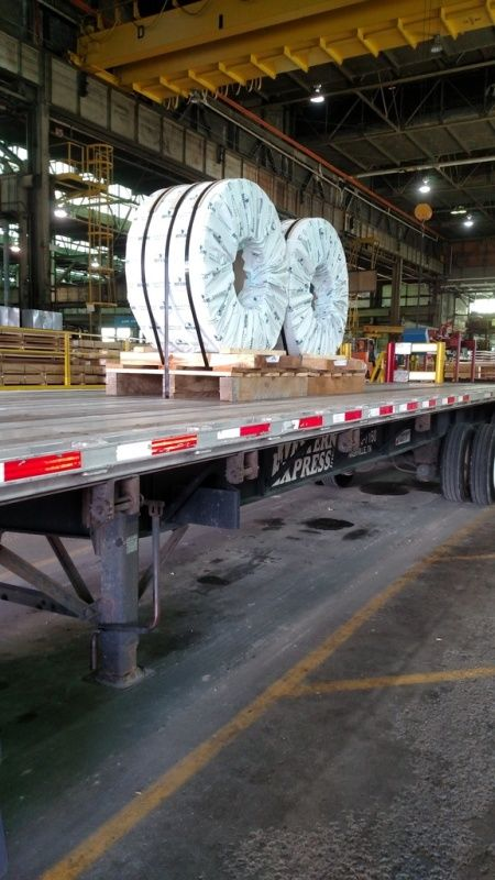 metal coils loaded and strapped with eyes horizontal on flatbed trailer