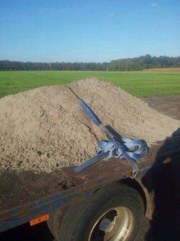 funny trucking pictures pile of dirt on flatbed trailer with strap on it
