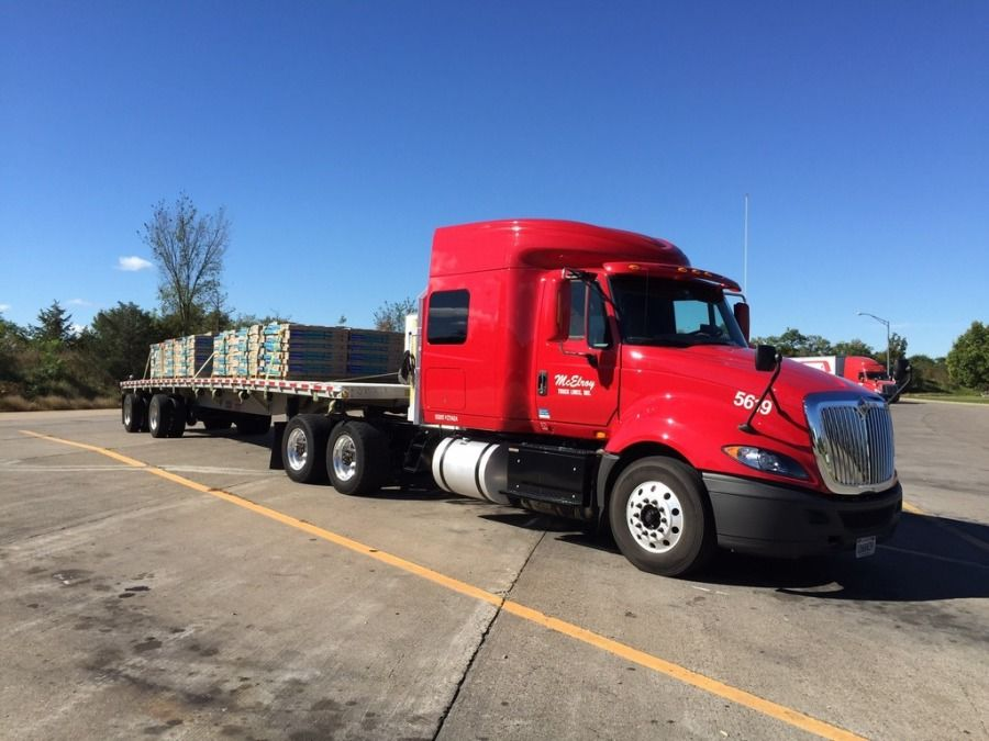 red McElroy truck with a loaded and secured flatbed trailer on a sunny day