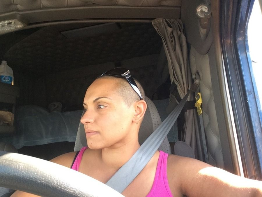 woman truck driver with shaved had behind the wheel in the cab of her truck