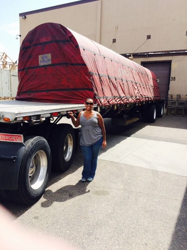 short lady truck driver standing next to a loaded and tarped flatbed trailer of paper rolls