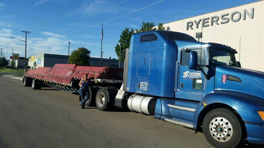lady truck driver with flatbed trailer loaded with aluminum
