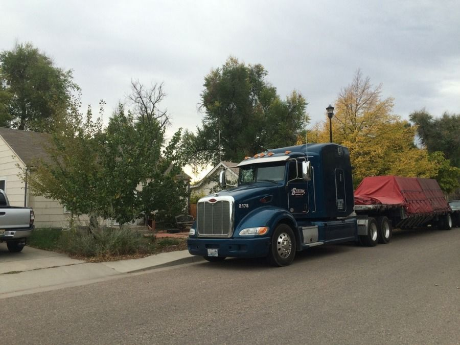 blue big rig pulling a loaded tarped flatbed trailer