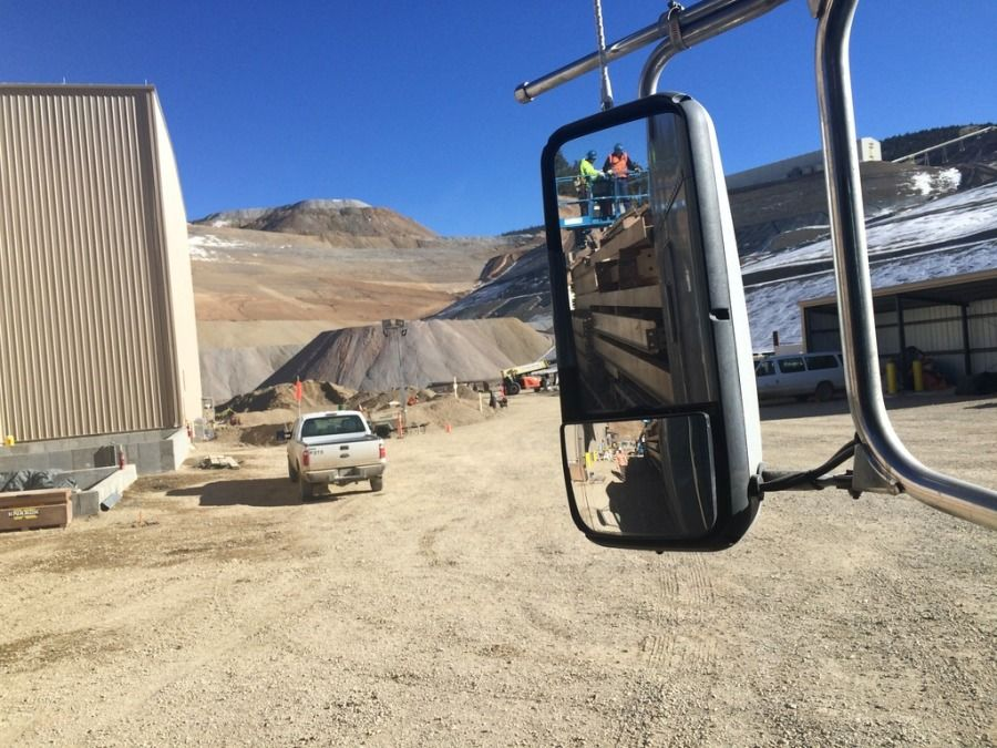 female truck driver's picture out the window at dump trucks loading at giant sand pit