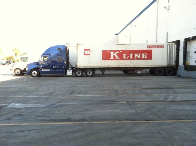 Kline reefer container unit backed up to the dock with a blue rig