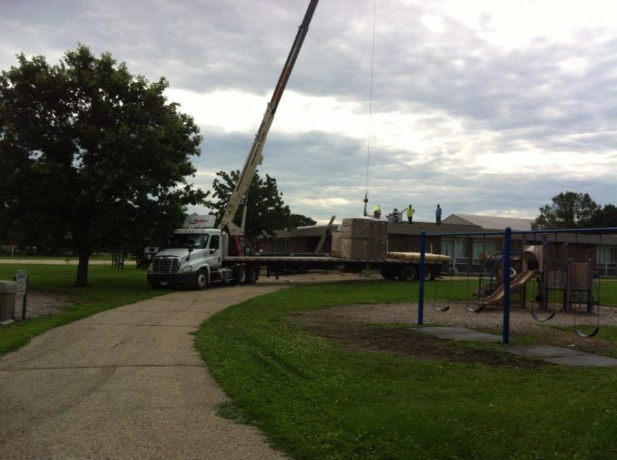 crane unloading construction supplies and wood off flatbed trailer at house