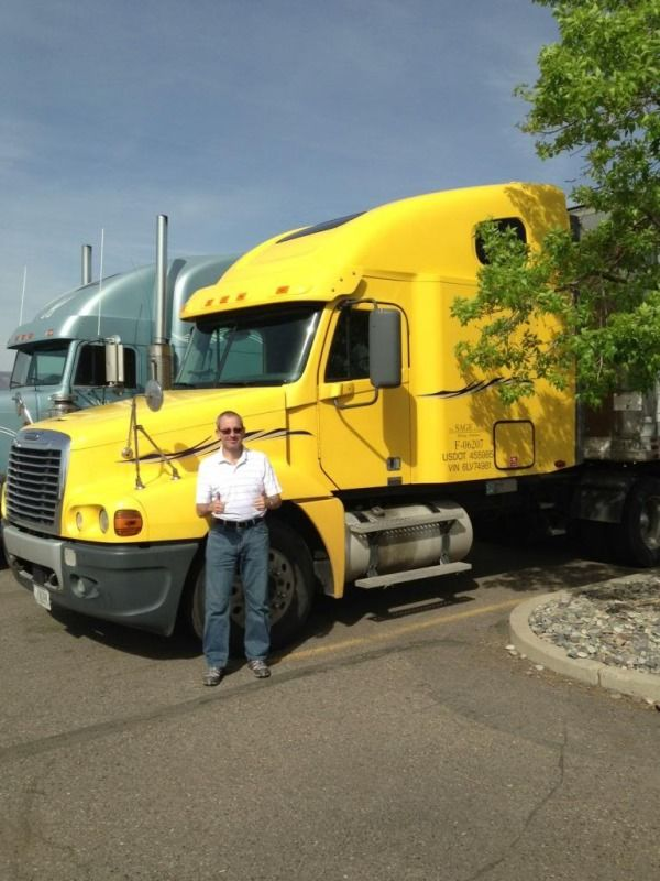 truck driver standing in front of yellow truck at trucking school