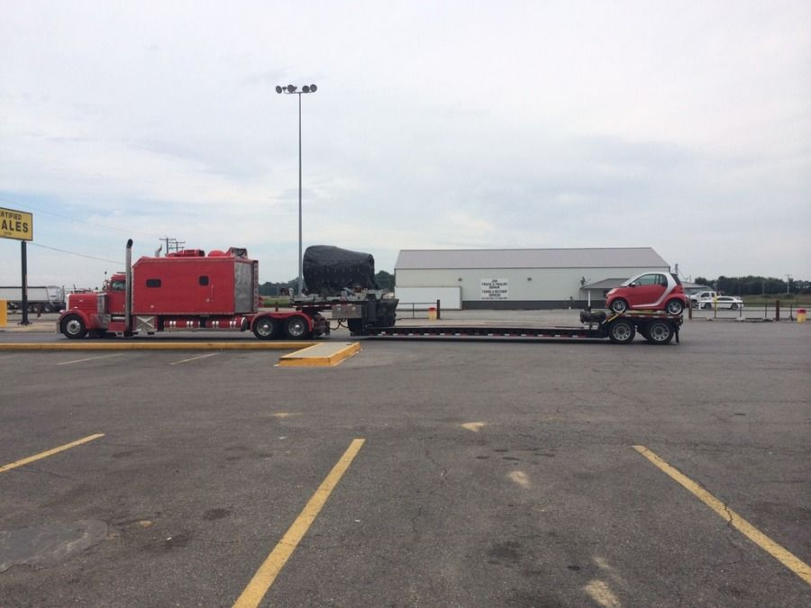 huge red big rig truck and flatbed trailer combo with tiny little smart car loaded on it