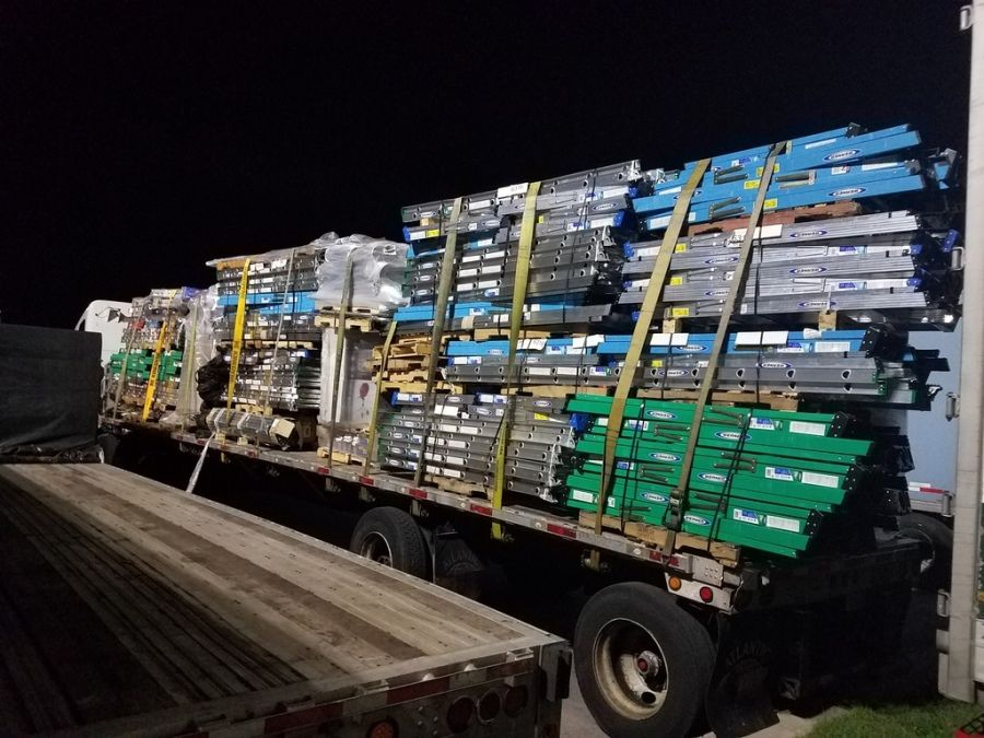 flatbed trailer loaded and strapped with stacks of ladders