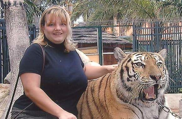 Rainy is a female truck driver sitting next to a tiger.