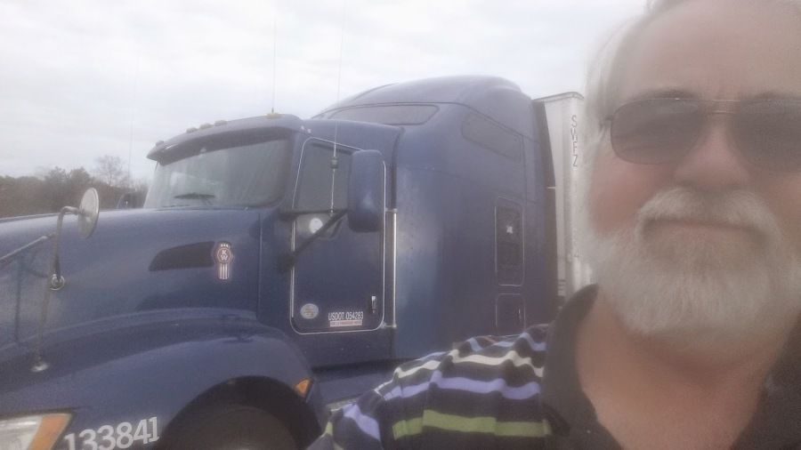 driver takes selfie standing in front of his truck