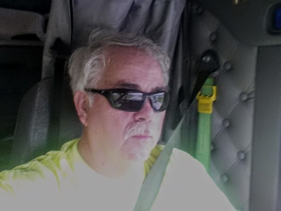 photo of older truck driver in the cab behind the wheel
