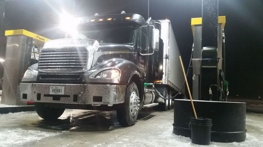 black Freightliner filling up at fuel island after ice storm