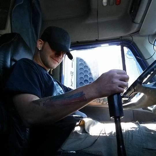 young truck drivers selfie in the cab of his truck