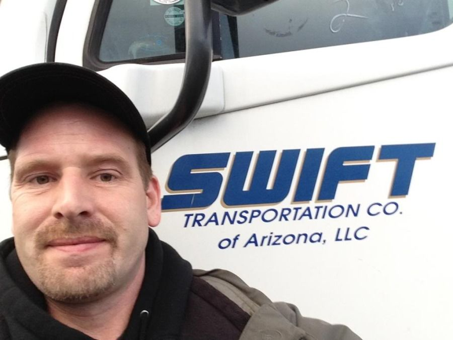 Swift transportation truck driver standing in front of his truck