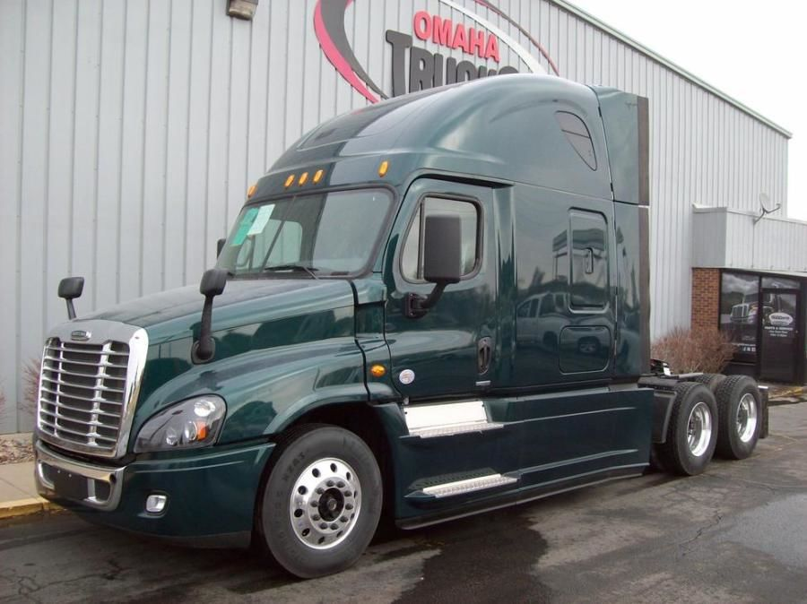 dark green Freightliner lightweight semi truck at dealer