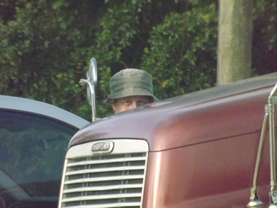 guy with hat hiding behind freightliner truck like Wilson from home improvement