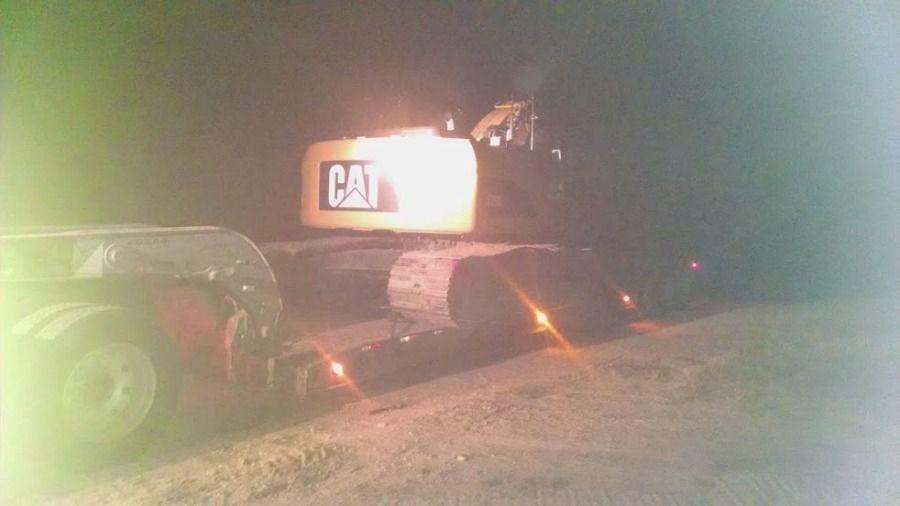 Caterpillar back-hoe loaded on flatbed trailer