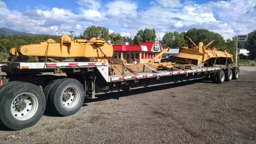 flatbed trailer loaded with dozer blade ripper and blade arms in New Mexico