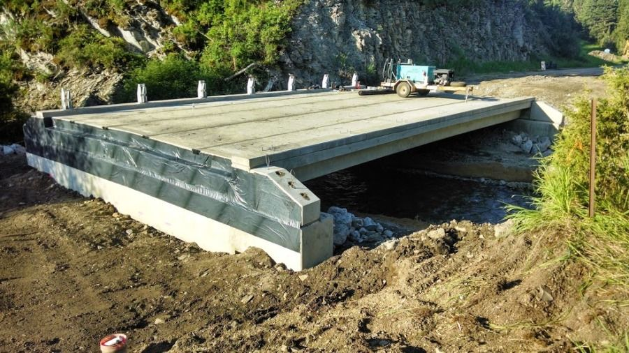 new bridge section being built over a stream