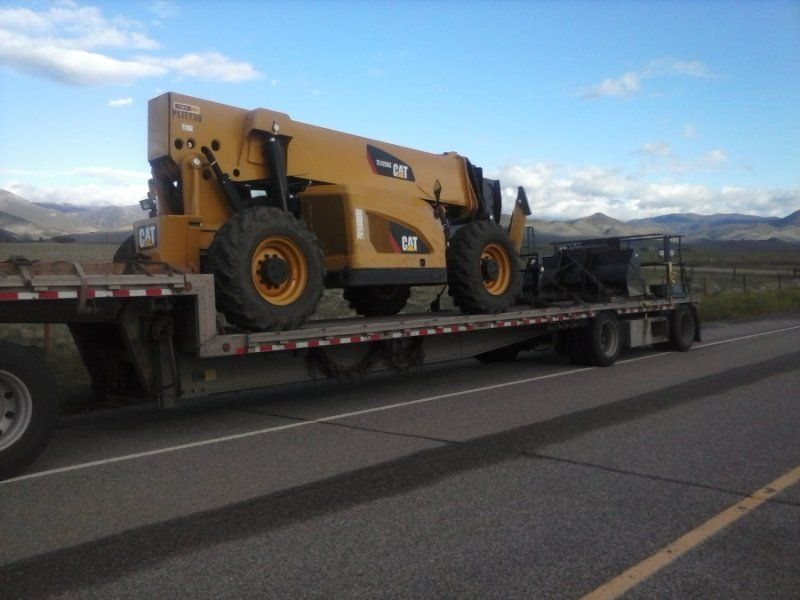 flatbed trailer loaded with heavy machinery
