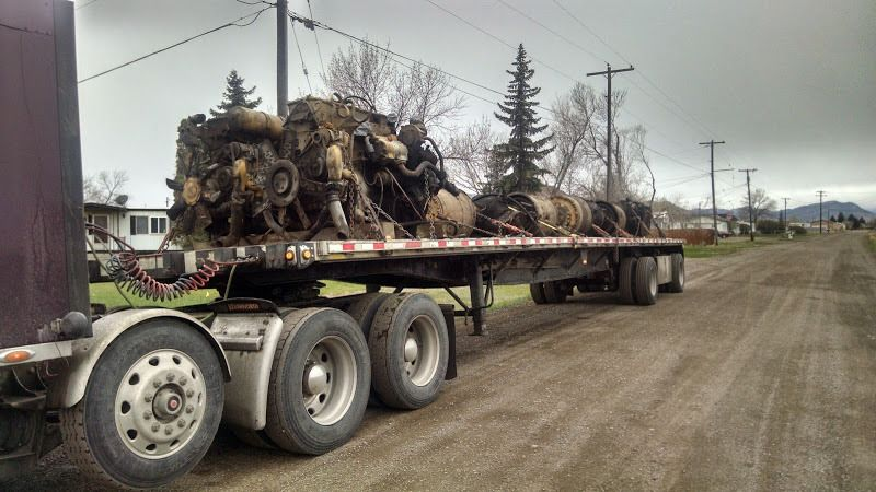 large motors chained to a flatbed trailer