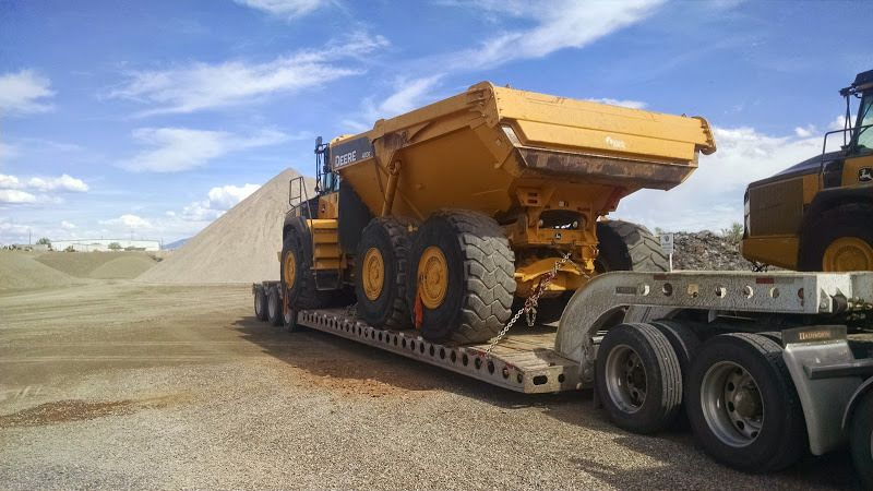 heavy-duty giant oversized dump-truck loaded on flatbed trailer